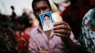 A relative holds a picture of a missing garment worker, who was working in the Rana Plaza building when it collapsed, in Savar, 30 km (19 miles) outside Dhaka April 24, 2013. The eight-storey block housing factories and a shopping centre collapsed on the outskirts of the Bangladeshi capital on Wednesday, killing more than 70 people and injuring hundreds, a government official said. REUTERS/Andrew Biraj (BANGLADESH - Tags: DISASTER BUSINESS)